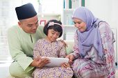 stock photo of malay  - Southeast Asian family using tablet pc computer at home - JPG