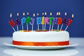 image of unhealthy lifestyle  - Happy birthday candles on a white cake over blue background - JPG