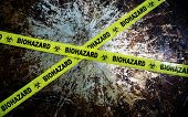 pic of biohazard symbol  - Yellow biohazard tape across and grunge metal background - JPG