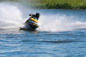 image of ski boat  - Man on jet ski turns left with much splashes - JPG