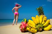 stock photo of idealistic  - Tropical fruits and a woman in a bikini sunbathing on the beach on sea background - JPG