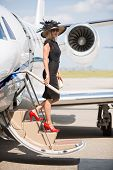 Side view of wealthy woman disembarking private jet at airport terminal