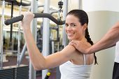foto of shoulders  - Fit brunette using weights machine for arms with trainer touching shoulders at the gym - JPG