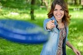 stock photo of frisbee  - Young woman outdoor throwing a frisbee in the park - JPG
