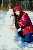image of biracial  - Young biracial Asian girl in red jacket playing outdoors in snow - JPG