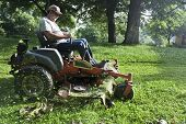 stock photo of grass-cutter  - Landscaper cutting grass on riding lawn mower