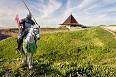 stock photo of knights  - Armored knight on warhorse over old medieval castle (fortress)