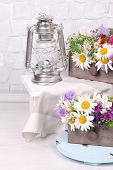 pic of kerosene lamp  - Beautiful flowers in crates with kerosene lamp on wooden stand on light background - JPG