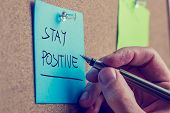 stock photo of instagram  - Retro instagram style image of a male hand writing Stay positive on blue post it paper pinned on cork bulletin board - JPG