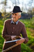 picture of scythe  - Old caucasian farmer sharpening his scythe to mow the land traditionally - JPG