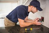 stock photo of check  - Hands checking the connections of electrical cables in the kitchen - JPG