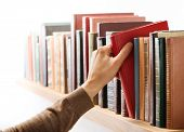 picture of book-shelf  - Hand taking book from the shelf - JPG