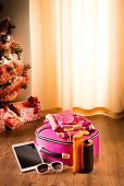 foto of sun tan lotion  - Christmas sun holidays with tablet luggage sunglasses and sun lotion decorated tree on background - JPG