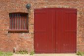 picture of red barn  - Red painted wooden barn door and window with bars in old brick wall to quayside building at Dell Quay in Chichester Harbour - JPG