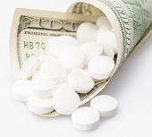 stock photo of drug dealer  - Rolled hundred dollars bill containing white drugs or medicine pills - JPG
