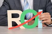 picture of arrow  - Midsection of businessman holding ROI  - JPG