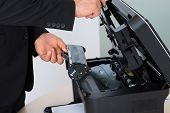 foto of cartridge  - Midsection of businessman fixing cartridge in photocopy machine at office - JPG