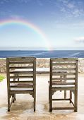stock photo of beachfront  - old wooden chairs and table at beachfront - JPG