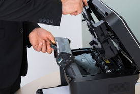 picture of cartridge  - Midsection of businessman fixing cartridge in photocopy machine at office - JPG