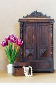 image of wardrobe  - Bright purple flowers tulips white vase vintage old wardrobe and wooden chest with pearls - JPG