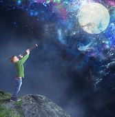 foto of fascinator  - Child fascinated watching the moon with binoculars - JPG
