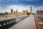 stock photo of westminster bridge  - Long exposure of the Houses of Parliament in London with blue sky seen from the Westminster Bridge with some blurred people - JPG