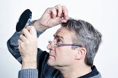 picture of dandruff  - Guy checking out his hair with a mirror - JPG