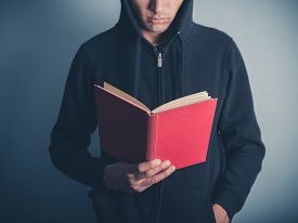 stock photo of anarchists  - A young man wearing a hooded top is standing around and is reading a red book - JPG