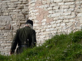stock photo of ecclesiastical clothing  - the monk in black leaves to conventual wall - JPG