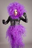 image of transexual  - Drag queen in violet dress standing on gray background - JPG