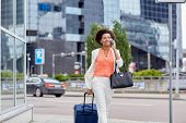 travel, business trip, people and technology concept - happy young african american woman with trave poster