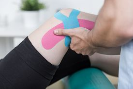 picture of physiotherapist  - Physiotherapist training with patient after knee injury - JPG