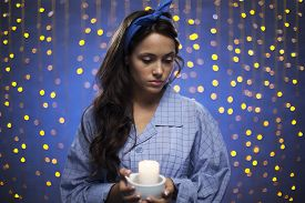 stock photo of pyjama  - Young female in pyjamas holding candle on sparkling background - JPG