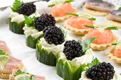 stock photo of crudites  - A plate of deliciously looking party snacks including cucumber with creamcheese and blackberries salmon toast and herring - JPG