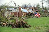SAINT LOUIS, MISSOURI - APRIL 24: A US flag flies amidst damaged homes  after tornadoes hit the Brid