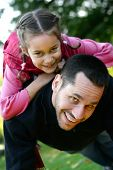 picture of priceless  - Young father lifting his daughter up on his back as they play together in the park - JPG