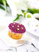 Single pretty cupcake with purple frosting served with cup of coffee, outdoor setting