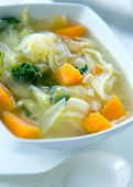 A bowl of healthy cabbage and sweet potato soup with parsley.