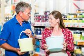 Home improvement couple, woman and man, in hardware store arguing about color of paint for renovatin poster