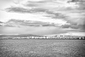 City On Sea Coast Iceland. Scandinavian Seascape Concept. Calm Water Surface And City With High Buil poster