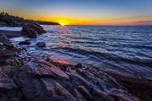 Rocky Coastal Sunset Landscape. Sunset Over The Horizon Of Lake Superior With A Rocky Coastline In T poster