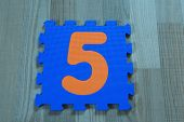 Blue Puzzle Piece With Orange Number Five On Wooden Texture Laminate Floor Indoors. 5th Birthday, An poster