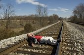 foto of imbecile  - a man lays on railroad tracks on a sunny day - JPG