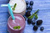 Blueberry And Blackberry Smoothie On Blue Wooden Background. Milkshake With Fresh Berries. Healthy B poster