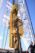 foto of oil rig  - an upward view of a top drive unit on a drilling rig - JPG