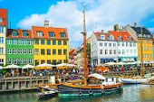 Scenic Nyhavn View With Boats By Embankment In Bright Sunshine, People Walking And Sitting In Restau poster
