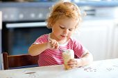 Adorable Baby Girl Eating From Spoon Sweet Ice Cream In Waffle Cone. Food, Child, Feeding And Develo poster