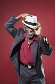 stock photo of fedora  - Cheerful senior man in suit adjusting fedora against red background - JPG