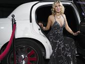 stock photo of limousine  - Beautiful young woman in evening wear getting out of limousine - JPG