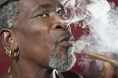 stock photo of exhale  - Closeup of a senior man exhaling cigar smoke against red background - JPG